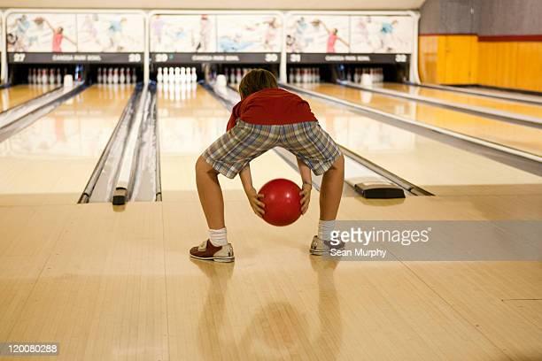 Boy bowls red bowling ball down a bowling lane