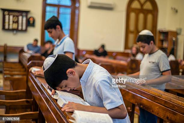 A boy bows for prayer during Mincha service in the Sixdomed Synagogue in Qrmz Qsb or Red Town Quba district of Azerbaijan on 28 September 2016 Qrmz...