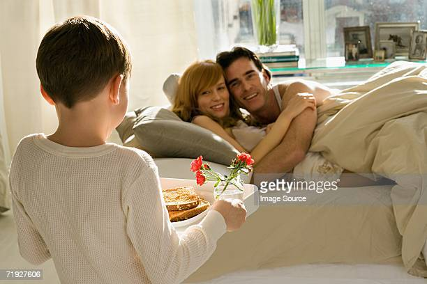Boy bringing breakfast to parents in bed