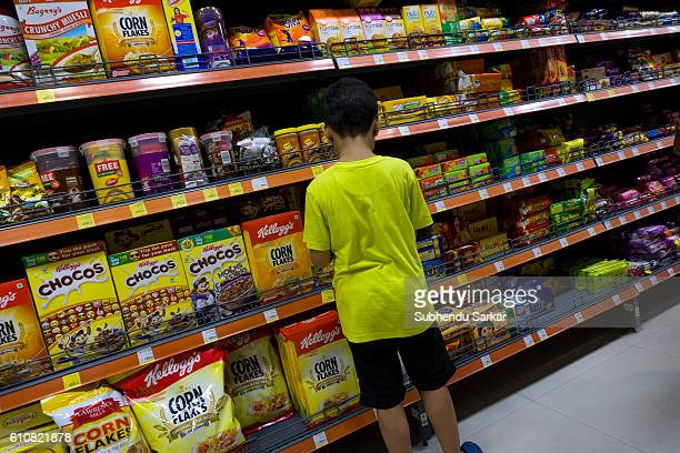 A boy browses food products on the shelves of a big supermarket