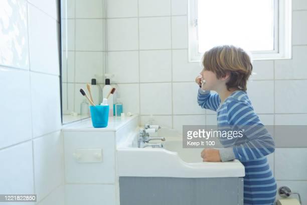 boy brushing his teeth - ナイトウェア ストックフォトと画像