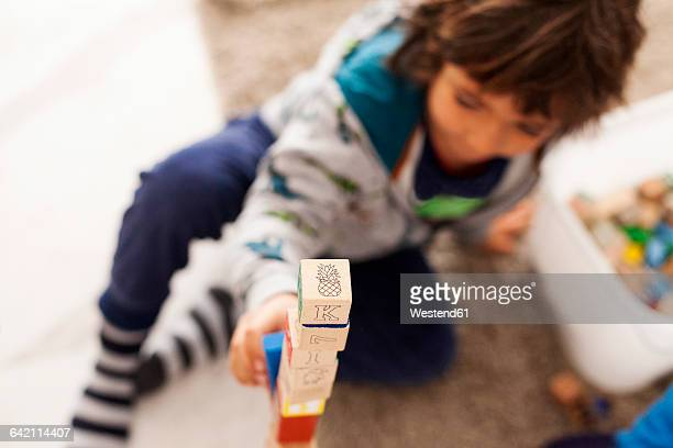 Boy building a tower with building blocks