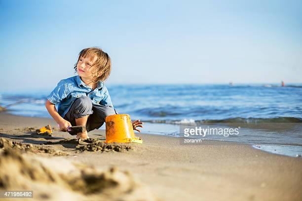 Boy building sandcastle