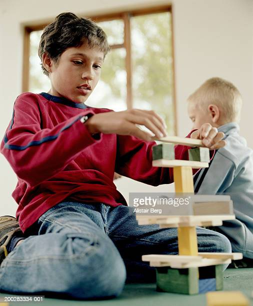 Boy (10-12) building tower from toy building blocks, ground view