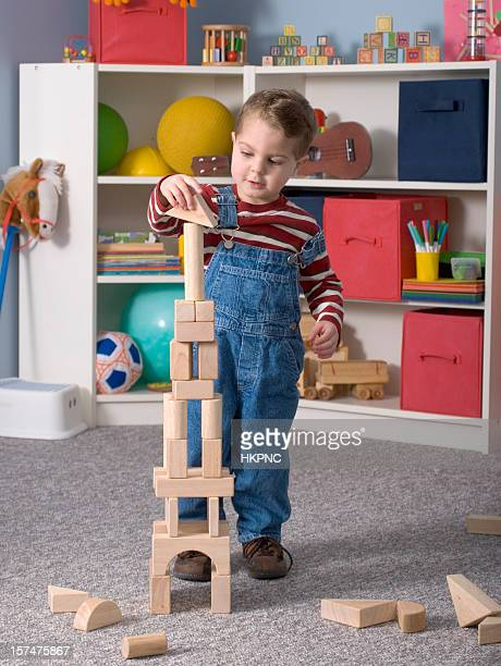 Boy Building With / Looking At Wooden Toy Blocks, Close, Vertical