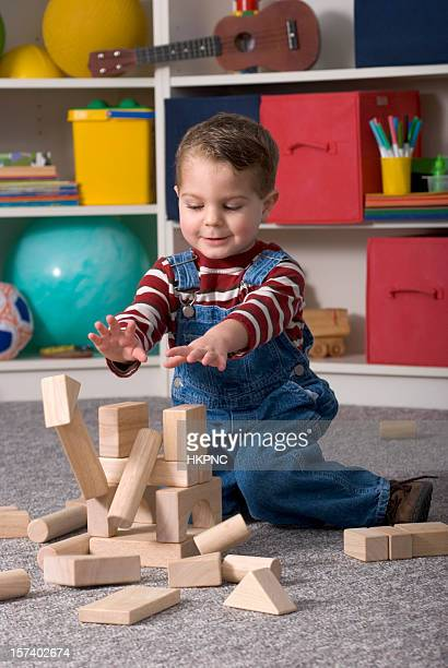 Boy Building With Wooden Toy Blocks Knocks Over His Tower