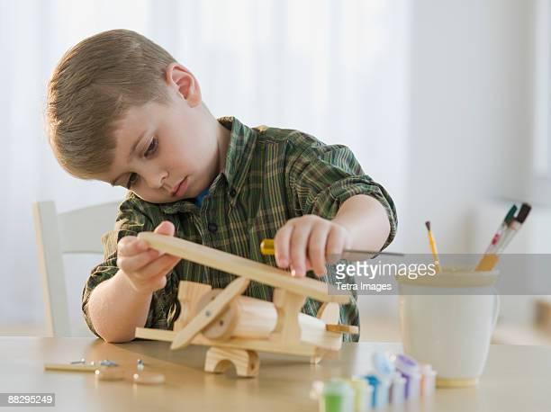 Boy building wooden airplane model