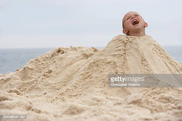Boy (2-4) buried in mound of sand, shouting (Digital Composite)