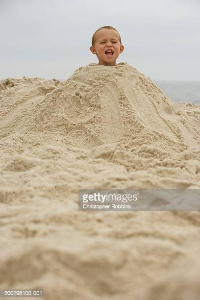 boy (2-4) buried in mound of sand, shouting, portrait - 埋まる ストックフォトと画像