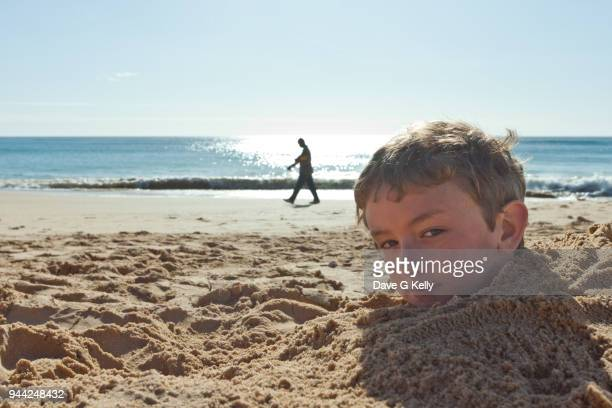 Boy buried in sand on beach