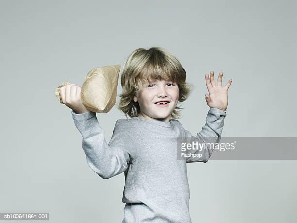 Boy (6-7) bursting paper bag, smiling, portrait