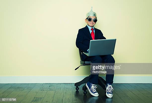 Boy Businessman Sits in Chair with Laptop and Tinfoil Hat