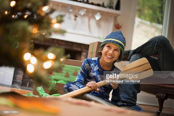 Un niño en un árbol de Navidad desenrollar un regalo, de madera de remo.