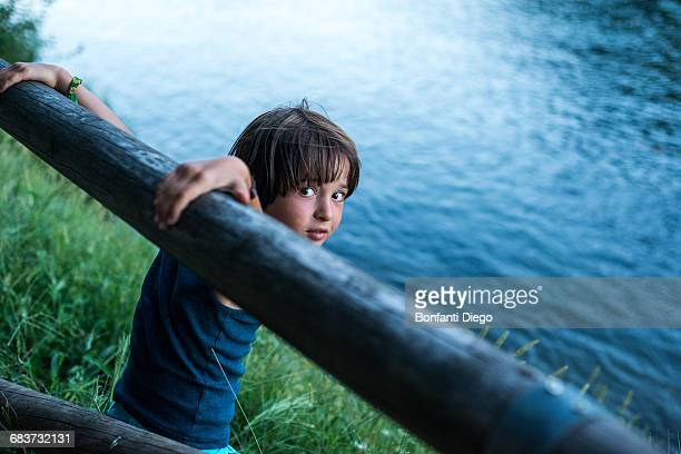 Boy by river looking over shoulder at camera