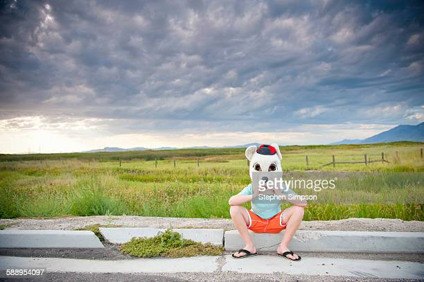 boy, 10, by the roadside with bear costume head