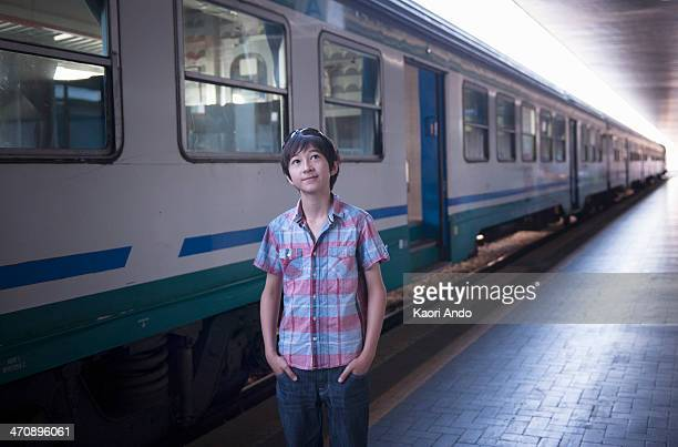 Boy by train with hands in pockets