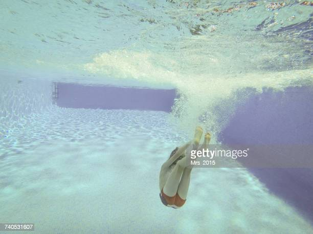 Boy cannonball diving into a swimming pool