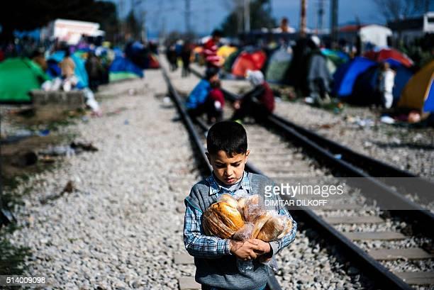 A boy caries bread at the makeshift camp of the GreekMacedonian border near the Greek village of Idomeni on March 6 where thousands of migrants and...