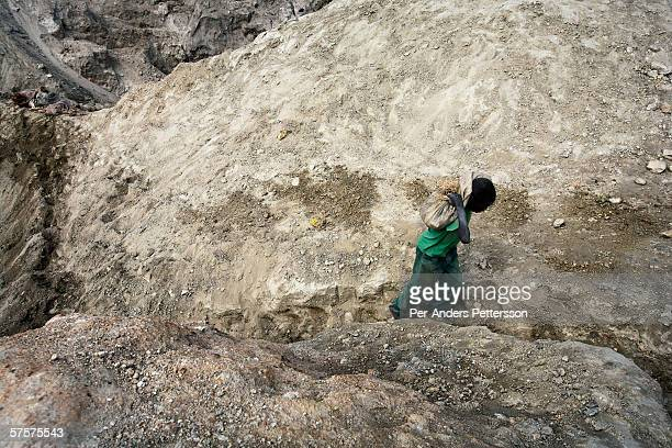 A boy carries a bag of copper on December 13 2005 in Ruashi mine about 20 kilometers outside Lubumbashi Congo DRC About 4000 artisan miners work here...