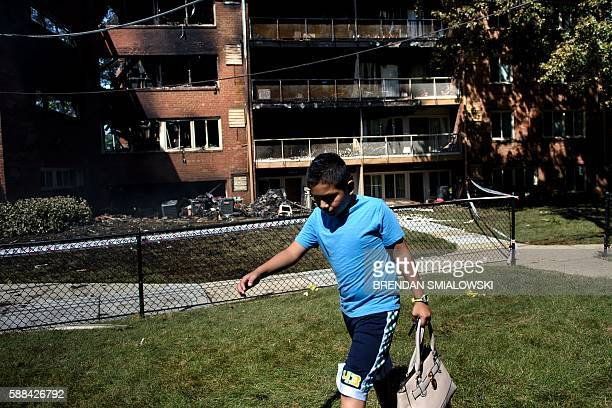 A boy carries a bag past burnt out apartment building after an explosion at Flower Branch Apartments August 11 2016 in Silver Spring Maryland / AFP /...