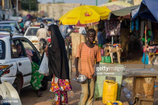 Boy carries a bowl in the market, as Nigeriens struggle to cope with the challenges of daily life in the second-poorest country in the world, made...