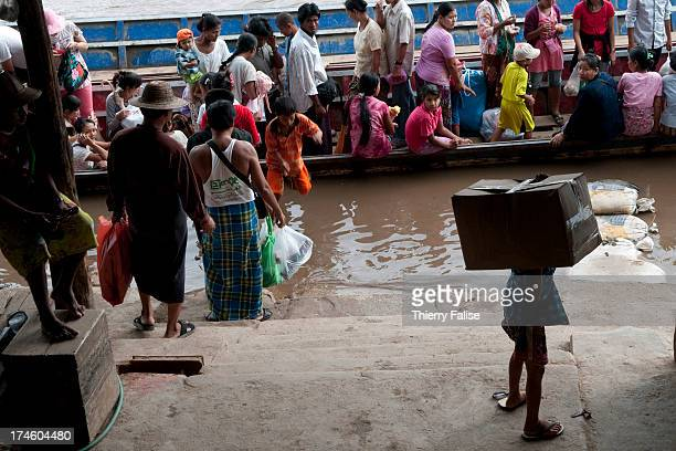 A boy carries a box before embarking in a boat across the Moei River marking the border between Thailand and Myanmar
