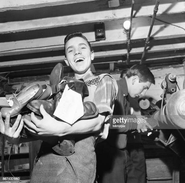 A boy carries a bundle of shoes He is 'at work' at the Lion Boys Club in Hoxton London where members do shoe repairs for old age pensioners free of...