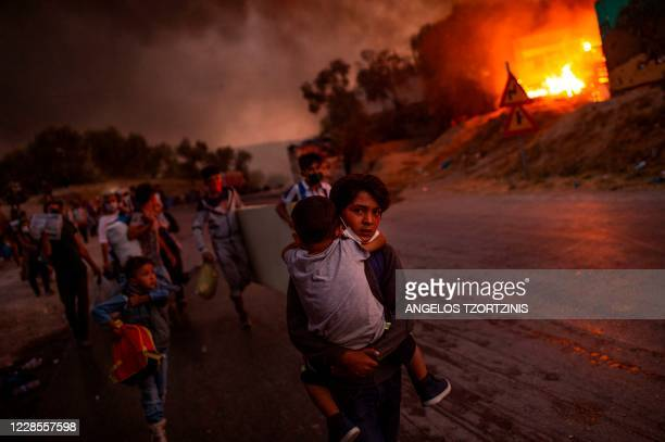 Boy carries a child in his arms as migrants flee the Moria camp after a fire broke out, on the island of Lesbos on September 9, 2020. - Thousands of...