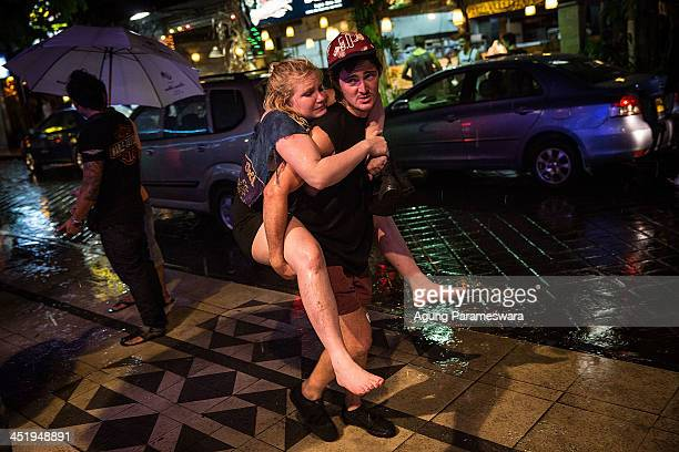 A boy carries a girl on his back after leaving a party during Australian 'schoolies' celebrations following the end of the year 12 exams on November...