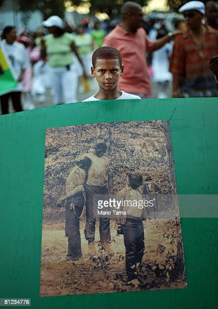 A boy carries a historical photograph of a lynching during the annual Super Sunday second line parade May 25 2008 in New Orleans Louisiana The parade...