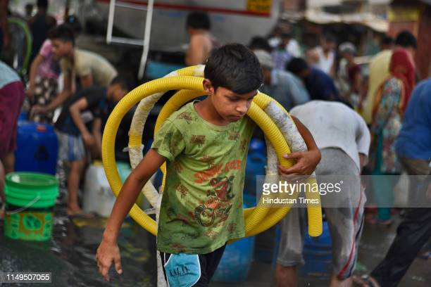 Boy carries a length of hose pipe to be used to fill water from a Delhi Jal Board tanker, at Sanjay Colony in Okhla Phase II, on June 12, 2019 in New...