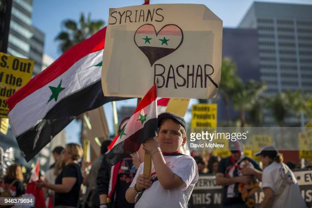 A boy carries a sign and flag as supporters of Syrian president Bashar alAssad protest the USled coalition attack in Syria on April 14 2018 in Los...