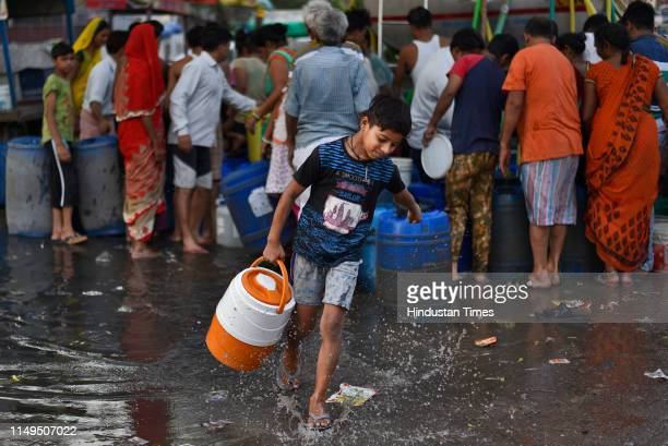 Boy carries a water container after filling it from a Delhi Jal Board tanker at Sanjay Colony in Okhla Phase II, on June 12, 2019 in New Delhi,...