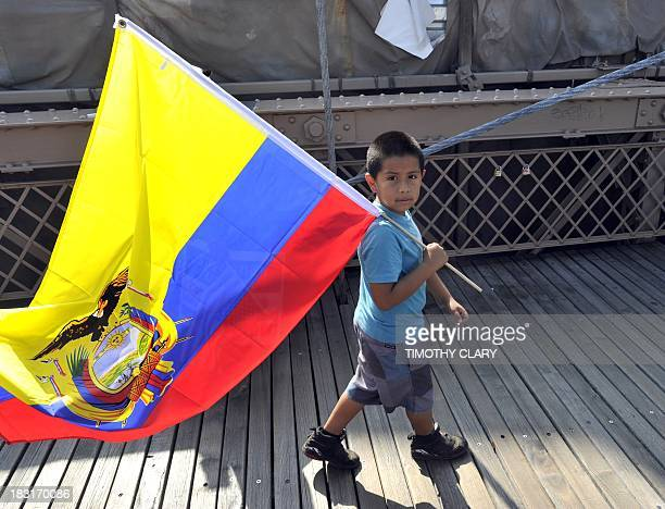 A boy carries an Ecuadorian flag as demonstrators march across the Brooklyn Bridge in New York on October 5 2013 as more than 80 demonstrations take...