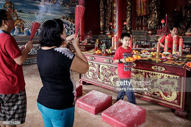 A boy carries an offerings as he attends prayers during Chinese New Year celebrations for the Year of The horse at Satya Dharma Temple on January 31...