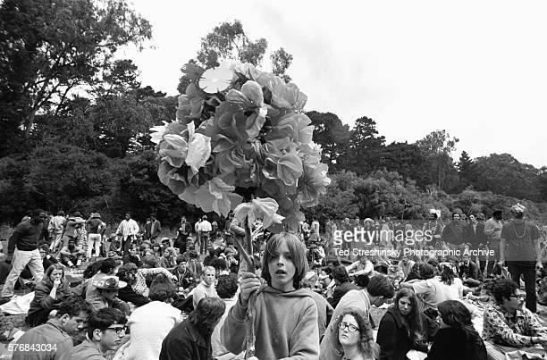 A boy carries bunch of paper flowers on a pole at a summer solstice celebration at Golden Gate Park in San Francisco