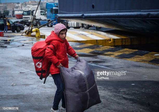 A boy carries his belonging items towards a coach bus following they disembark at the Port of Piraeus 29 September 2018 Thousand migrants and...