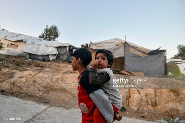 Boy carries his brother in a camp outside of the refugee camp of Moria, in the northern Greek island of Lesbos on September 25, 2018. - Despite a...