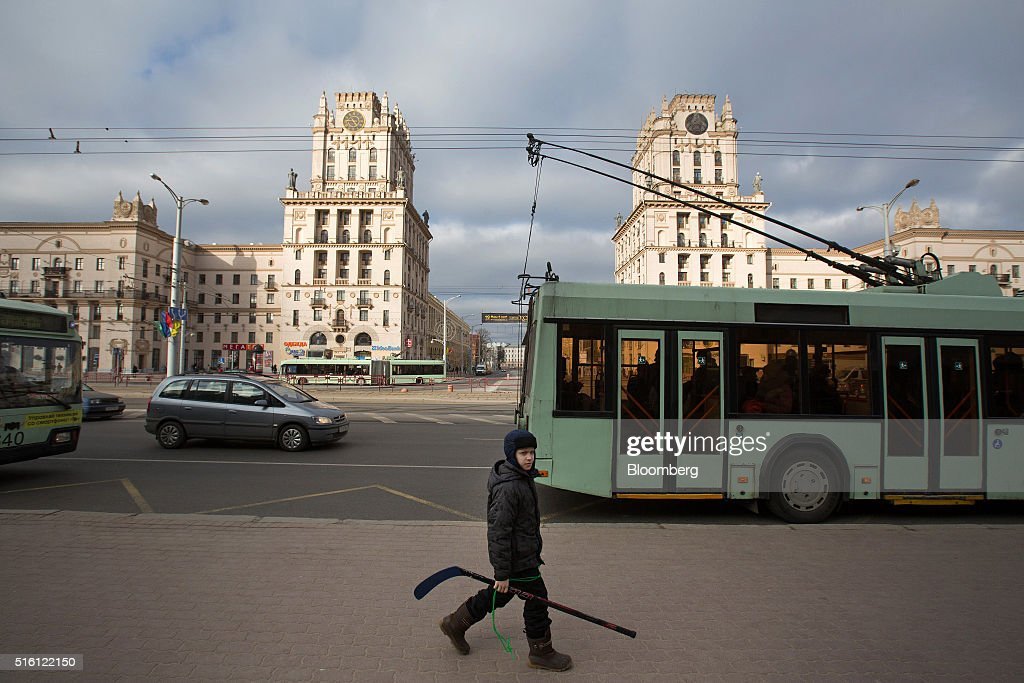 A boy carries his ice hockey stick along a sidewalk past the Gates of Minsk, center, in Minsk, Belarus, on Wednesday, March 16, 2016. European Union governments scrapped sanctions on leaders of Belarus in an effort to pry the former Soviet republic out of the shadow of the Kremlin. Photographer: Andrey Rudakov/Bloomberg via Getty Images
