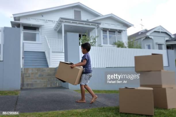 boy carries moving box into his new home - rafael ben ari imagens e fotografias de stock