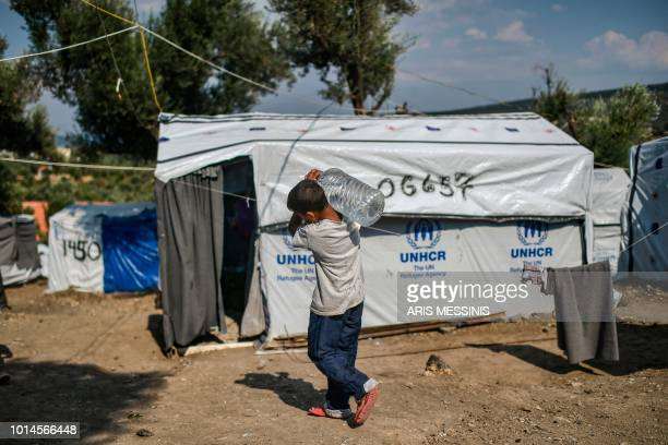 A boy carries water bottle at a camp outside the Moria refugee camp in the island of Lesbos on August 05 2018