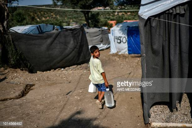 A boy carries water bottles at a camp outside the Moria refugee camp in the island of Lesbos on August 5 2018