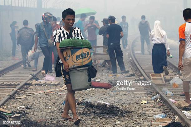 A boy carry their belongings past railway track after fire in a slum area Fire destroyed approximately 100 wooden dwellings built along a busy...