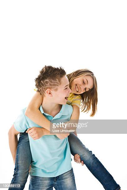 a boy carrying a girl piggyback - little girls bare bum stock pictures, royalty-free photos & images