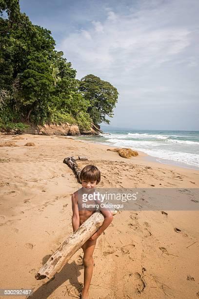 Boy carrying a log on a beach