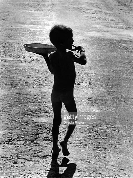 A boy carrying a plate on a road in Assam India 1978