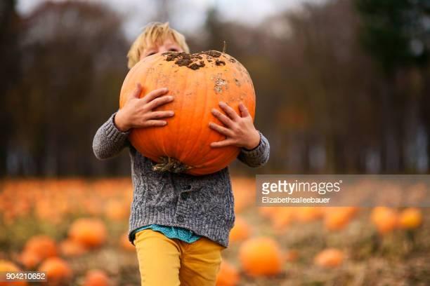 Boy carrying a pumpkin in a pumpkin patch