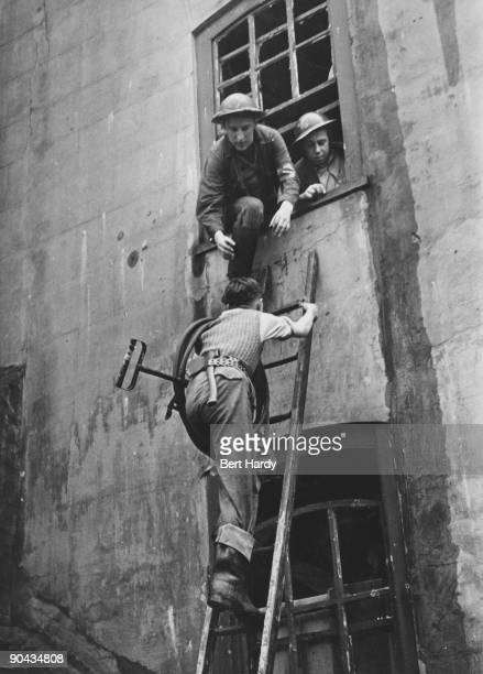 A boy carrying a stirrup pump up a ladder to tackle a fire after an air raid on the East End of London April 1941 He and his colleagues are members...
