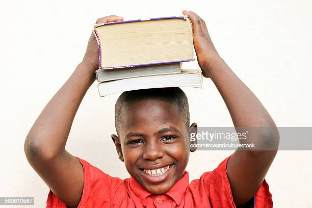 A boy carrying books on his head