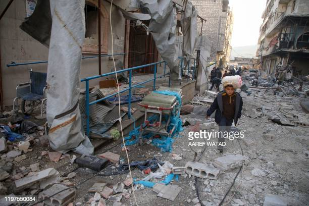 Boy carrying bread on his head walks past a medical clinic, damaged in reported airstrikes, in the rebel-held town of Ariha in the northern...